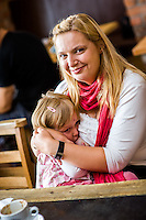 Mothers who have come together to celebrate the annual Big Latch On breastfeeding promotion event breastfeeding in a cafe. 