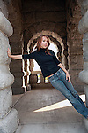 beautiful young woman with long brown hair stretching in a stone archway