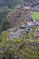 Peru, Machu Picchu.  Rock Quarry in Center.  People in Sacred Plaza, upper-right center.  Intiwatana (Hitching Post of the Sun), upper background.