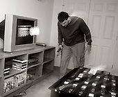 """Spike excited by his choice of video is full of anticipation and can't contain himself down stairs in his basement in Cranbury, NJ., on Saturday December 4, 2005. Adults and children alike who have autism, prefer their lives to be structured and in order. Spike is no different, his videos are lined up neatly on the coffee table in the basement where Spike is left to """"rock  out"""" to his movies.  Spike who is verbal has the ability to make simple sentences although does not engage in lengthy conversation. Spike has had therapy at an early age due to a large part in his mother's devotion to get Spike the proper care that was needed. Early intervention is so important in autism resulting in correct synaptic impulses in the brain and may contribute to the lessen of severity of autism. photo by jane therese..."""