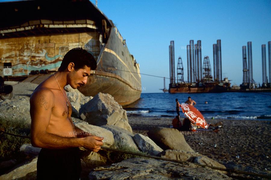 1997..Despite pollution, Azerbaijanis sunbathe on a beach facing Baku's oil plants in the Caspian Sea. ...Malgré la pollution, des Azerbaïdjanais prennent un bain de soleil sur une plage face aux installations pétrolières de Bakou dans la mer Caspienne. .