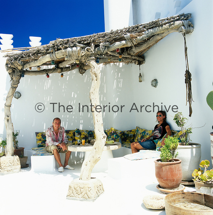 Portrait of Emma Wilson and Graham Carter sitting in the shade of a wooden awning on the roof terrace