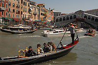 Gondolas and water taxis on the Grand Canal with the Rialto bridge in the background. Venice, Italy.
