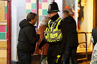 Pictured: A man is spoken to by a police officer in Wind Street, Swansea, Wales, UK. Friday 20 December 2019<br /> Re: Black Eye Friday (also known as Black Friday, Mad Friday, Frantic Friday) the last Friday before Christmas, in Swansea, Wales, UK.