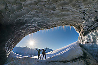 A couple stands at the entrance to a glacier ice cave in the Alaska Range mountains, Interior, Alaska.