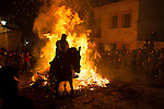 A man rides a horse through a bonfire during Las Luminarias celebration, as part of a ritual in honor of Saint Anthony the Abbot, the patron saint of domestic animals, in San Bartolome de Pinares, Spain. January 16, 2015. (ALTERPHOTOS/Victor Blanco)