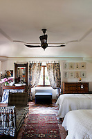 The guest bedroom features a daybed with vintage cushions and botanical drawings hanging above the antique chest of draws
