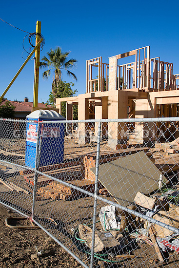 A building site of a large two-story wooden single family house. Large amounts of wood and other raw materials are being used to build this new house on a lot where a single-story home was demolished. Cupertino, California, USA