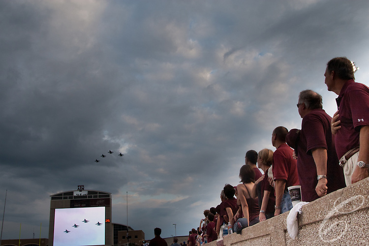 Fans sing the National Anthem as a flight of U.S. Marine Corps F-18's fly over Kyle Field prior to a Texas A&M home football game in 2007.