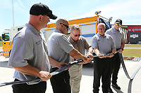 NWA Democrat-Gazette/DAVID GOTTSCHALK Captain Damon Lee (second from left), with the Springdale Fire Department, and former Chief Dan White uncouple a nozzle Thursday, July 11, 2019, during the ceremonial opening of the new Springdale Fire Department Fire Station 7. The station, located on Her-Ber Avenue, was made possible by the passing of the 2018 Bond.