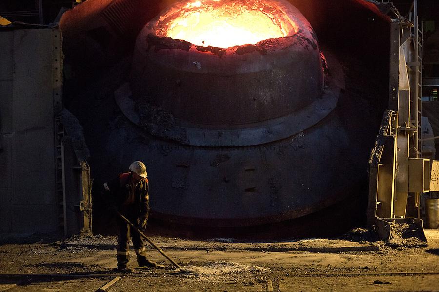 MARIUPOL, Ukraine: A worker is sweeping the iron that became after it filled over blast furnace. <br /> <br /> MARIUPOL, Ukraine: Un travailleur balaie le minerai de fer apr&egrave;s avoir d&eacute;bord&eacute; du haut fourneau.