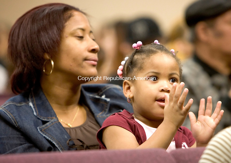 WATERBURY, CT- 06 JANUARY 2006-010607JS11-Scarlett Martinez, 3, applauds while she and her mother Angelica Martinez watch the Three Kings celebration at the Shekinah Christian Church in Waterbury on Saturday. <br /> Jim Shannon/Republican-American