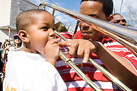 Father and son share a trombone in downtown New Orleans on Mardi Gras Day, February 28, 2006.  Many questioned the decision to stage a Mardi Gras in New Orleans a mere six months after the levees broke and inundated much of the city in water, but the show did go on in 2006.  Although the resources necessary to put on the city wide celebration were substantial and detractors pointed to the moral implications of throwing a party while so much of the city was in ruin, in the end most agreed it was the proper thing to do for the city, not only to attract much needed tourism (and hence business), but also to remind those residents that remained and those that had relocated why they loved their unique city and why it was worth fighting for.