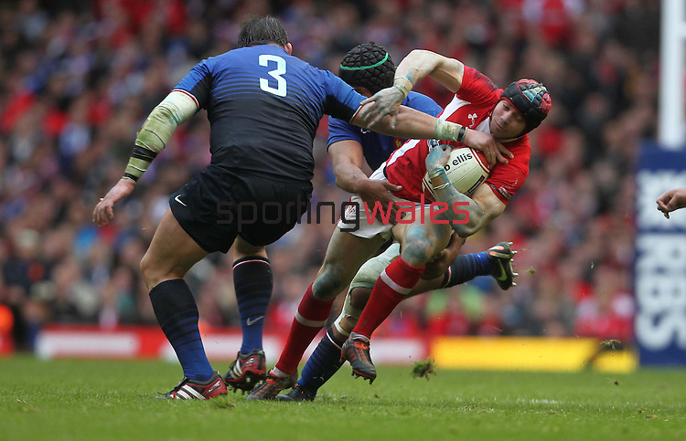 Leigh Halfpenny tries to avoid Thierry Dusautoir and David Attoub..RBS 6 Nations 2012.Wales v France.Millennium Stadium.17.03.12..CREDIT: STEVE POPE-SPORTINGWALES