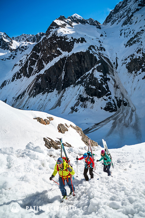 A group of ski tourers with their skis on their packs hiking up a steep section while on a ski tour of the Berner Haute Route, Switzerland