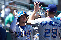 Willy Adames (27) of the Durham Bulls high fives teammate Ryan Yarbrough (29) after scoring a run against the Lehigh Valley Iron Pigs at Coca-Cola Park on July 30, 2017 in Allentown, Pennsylvania.  The Bulls defeated the IronPigs 8-2.  (Brian Westerholt/Four Seam Images)