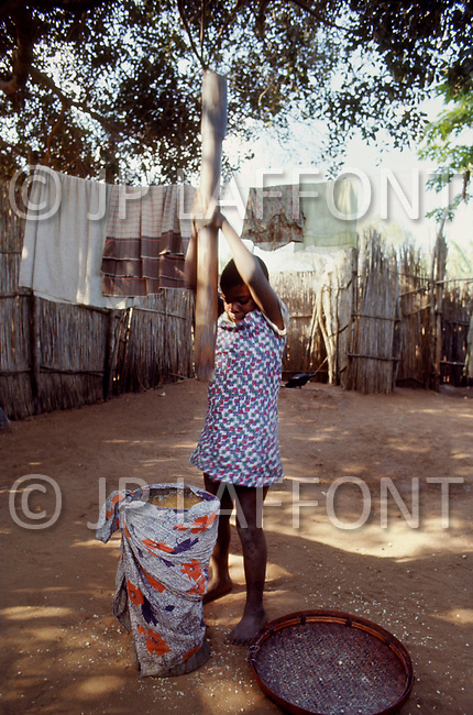 June 1975, Lourencio Marques (now Maputo), Mozambique. Strong children living in the poor suburbs of the city are sent to crush the roots of manioc plants to be used for cooking. The work is difficult, as the wooden pestle can often weigh twenty pounds or more, and though they work long hours, they are poorly paid.