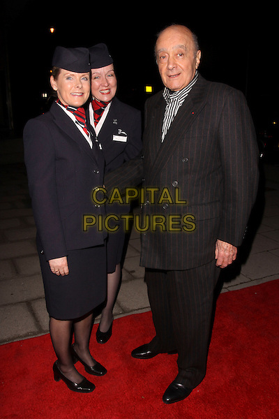 MOHAMED AL FAYED .At the Evening Standard Influentials Party, Altitude 360, Millbank Tower, London, England, UK, .16th November 2010..full length black pinstriped suit pinstripe shirt BA british Airways air hostesses stewardesses girls uniform hats .CAP/AH.©Adam Houghton/Capital Pictures.