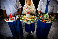 "10 year old Siti Nurmilah, tenth grade student at Kartini Emergency School, stands with her winning rice cone dish and the two other winners of the school cooking contest, part of events held to celebrate Indonesian Independence Day. Daughter of a truck driver, Nurmilah has been going to school at Kartini since she was in kindergarten. She says,""Thanks to the 'Twin Teachers', I now know how to cook, wash my own clothes, wash dishes, sew and paint clothes."" Since the early 1990s, twin sisters Sri Rosyati (known as Rossy) and Sri Irianingsih (known as Rian) have used their family inheritance to set up and run 64 schools in different parts of Indonesia, providing primary education combined with practical skills to some of the country's most deprived children."