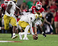 ATHENS, GA - SEPTEMBER 21: Ian Book #12 of the Notre Dame Fighting Irish recovers a fumbled snap against the Georgia Bulldogs during a game between Notre Dame Fighting Irish and University of Georgia Bulldogs at Sanford Stadium on September 21, 2019 in Athens, Georgia.