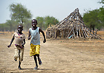 Children run past the ruins of homes in Leu, a village in the contested Abyei region along the border between Sudan and South Sudan. The village was looted and burned in 2011 when soldiers and militias from the northern Republic of Sudan swept through the area, chasing out more than 100,000 Dinka Ngok residents. A few thousand families have returned to the region since northern combatants withdrew in 2012, yet their life is precarious. In Leu, the Catholic Church rehabilitated a clinic and drilled a well. For political and logistical reasons, the Catholic Church is one of the few organizations willing to openly accompany the people of Abyei during these uncertain times.