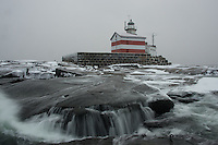 Waves run off the ice-coated skerry rocks at Märket lighthouse, Finland in winter.