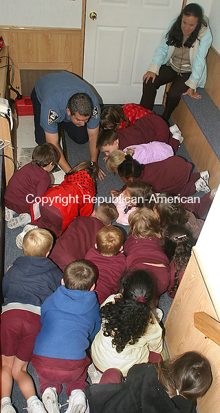 TORRINGTON, CT.-07 OCTOBER 2009-100709DA03-Torrington Firefighter Jeremy Minard instructs kindergarden students of St. Peter/St. Frances school in Torrington to crawl when they see smoke during a fire safety class Wednesday. The fire department brought a trailer that simulates a burning apartment for kids to flee from.<br /> Republican-American Darlene Douty