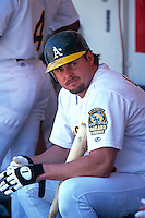 OAKLAND, CA - Jason Giambi of the Oakland Athletics sits in the dugout during a game at the Oakland Coliseum in Oakland, California in 2000. Photo by Brad Mangin