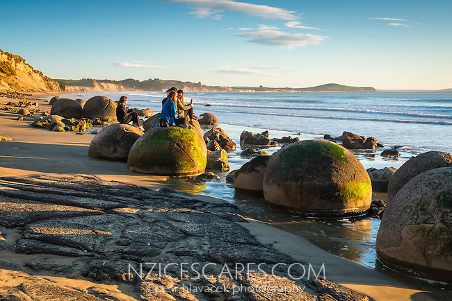 Group of girls watching rising sun at Moeraki Boulders, Moeraki, Otago, New Zealand