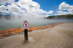 "A ""Do Not Walk"" danger sign sits next to the boiling and brilliantly coloured Champagne Pool at the geothermal site, Wai-O-Tapu Thermal Wonderland, near Rotorua on the North Island of New Zealand."