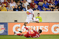 Dane Richards (19) of the New York Red Bulls jumps over a tackle by Gonzalo Segares (13) of the Chicago Fire. The New York Red Bulls and the Chicago Fire played to a 2-2 tie during a Major League Soccer (MLS) match at Red Bull Arena in Harrison, NJ, on August 13, 2011.