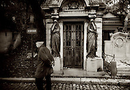 An old man walks past a doorway at the Pere Lachaise Cemetery in Paris, France