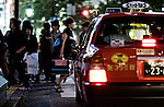 Against the backdrop of the almost permanent bustle of crowds, a cab waits for the lights to change at one arm of the enormous zebra-crossing in the famous Shibuya district of Tokyo.