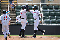 Micker Adolfo (27) of the Kannapolis Intimidators high fives teammate Brandon Dulin (31) as he crosses home plate after hitting a home run against the West Virginia Power at Kannapolis Intimidators Stadium on June 18, 2017 in Kannapolis, North Carolina.  The Intimidators defeated the Power 5-3 to win the South Atlantic League Northern Division first half title.  It is the first trip to the playoffs for the Intimidators since 2009.  (Brian Westerholt/Four Seam Images)