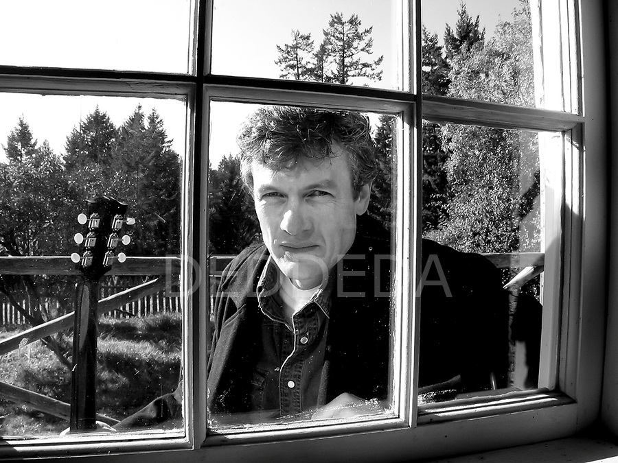 Musician Allen Dobb looks through a window of a heritage building near Victoria, British Columbia. Photo assignment for Allen Dobb CD cover and promotional materials.
