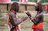 Lolgorian, Kenya. Two Maasai moran warriors in the manyatta temporary village discussing the Eunoto ceremony.