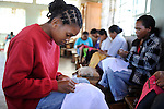 """MADAGASCAR Antananarivo, catholic priest Per Pedro Opeka has build Akamasoa a social community project with housing schemes, health units and schools for the poorest of Tana, women work in workshop / MADAGASKAR Pater Pedro Opeka hat die Gemeinde Akamasoa , auf madagassisch """"gute Freunde"""" , mit Muellsammlern, Bettlern und Sozialschwachen auf einem Huegel bei Antananarivo erbaut, Teil des Projektes sind Hausbau, Schulen, Krankenhaeuser und Beschaeftigung, Frauen arbeiten in Projektwerkstatt"""