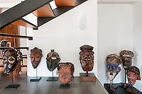 A selection of Congo masks from the owner's collection displayed on the floor under the staircase