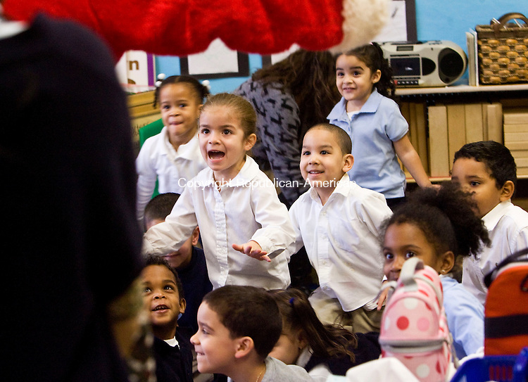 WATERBURY, CT - 18 DECEMBER 2008 -121808JT02-<br /> Pre-k students run to the outstretched arms of Santa Claus on Thursday as Santa walked into their classroom at Woodrow Wilson Elementary School in Waterbury. This was Santa's second annual visit in which he brought gifts from clothing distributer NEJ to every student at the school. From left, students are Loren Tuck, Jonathan Morkos below her, Alexander Aguero at bottom left, Nathalyn Rivera, Giovanny Alvarado below her, Ronald Chabla, Jayda Melendez behind him, Jomairy Perez and Bryant Marc Williams.<br /> Josalee Thrift / Republican-American