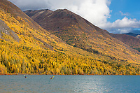 Kayakers Sonny and Claire Bartlett, enjoy an autumn day on Eklutna lake, Eklutna lake state park, just north of Anchorage, Alaska.