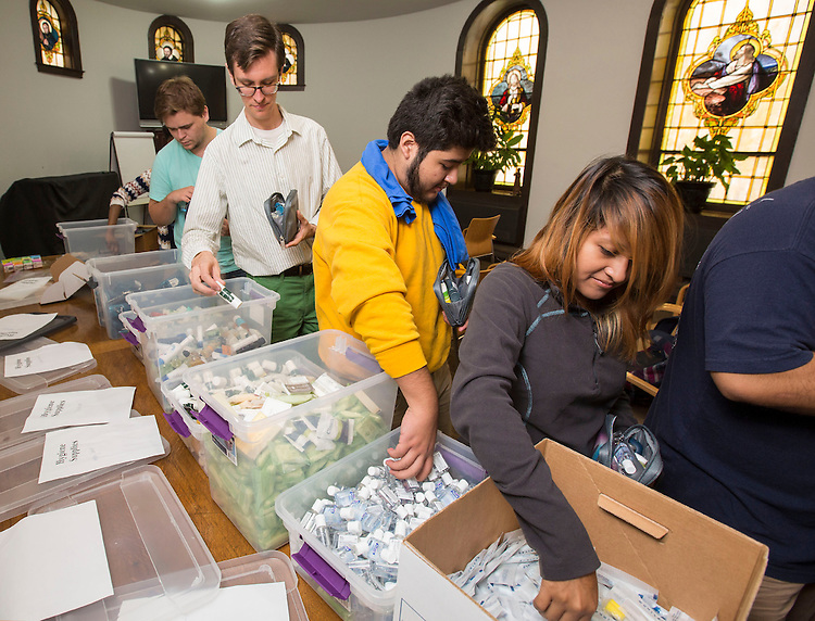 Albert Paljevic, Patrick Humpal, Milton Olivares and Jackie Diaz (left to right) work in assembly line fashion inside the St. Vincent de Paul Church Tuesday, Sept. 9, 2014, as they build small satchels of personal hygiene products for the needy during New Student Service Day. Student volunteers also delivered food to the church's Mother Seton Food Pantry and Sandwich Window which provides food for the hungry. (DePaul University/Jamie Moncrief)