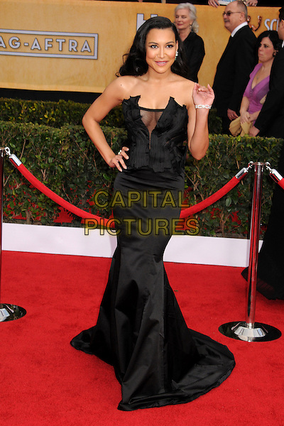 Naya Rivera (wearing Donna Karan).Arrivals at the 19th Annual Screen Actors Guild Awards at the Shrine Auditorium in Los Angeles, California, USA..27th January 2013.SAG SAGs full length black strapless dress satin silk corseted corset gown sheer accordion pleating decolletage hand on hip cleavage arm waving .CAP/ADM/BP.©Byron Purvis/AdMedia/Capital Pictures