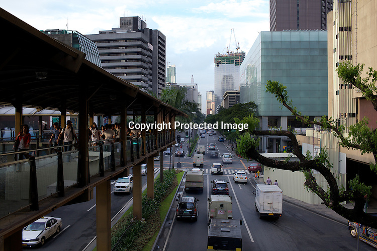 Pedestrians walk while the traffic moves smoothly around the shopping district of Greenbelt area in the city of Makati in Manila, Philippines. Photo: Sanjit Das