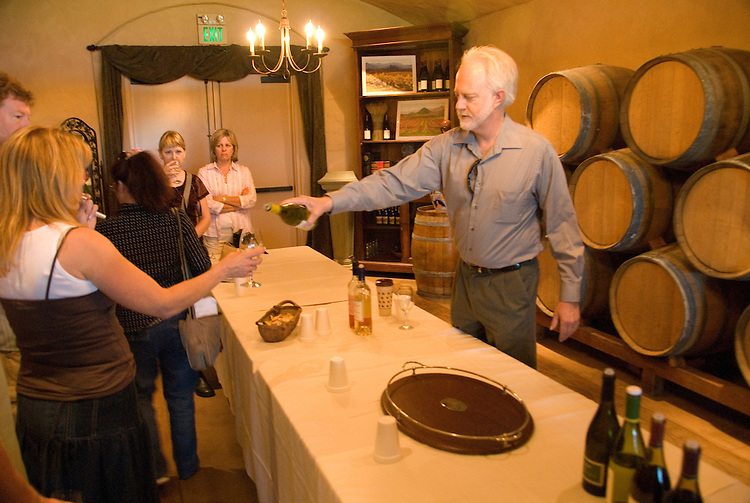 California, San Luis Obispo County: Winemaker Harry Hansen at Edna Valley Vineyards, noted for his Chardonnay.  Hansen pouring his wine in tasting room..Photo caluis114-70740..Photo copyright Lee Foster, www.fostertravel.com, 510-549-2202, lee@fostertravel.com