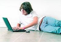 Teenage boy laying on floor working on laptop computer