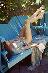 Sensual erotic portrait of a beautiful sexy half naked young woman lying asleep on a bench in a garden with an open book in her hand