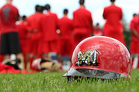Batavia Muckdogs team meeting in the background of a helmet waiting to see some game action during the first day of practice for the start of the NY-Penn League season at the Dwyer Stadium in Batavia, New York;  June 13, 2011.  Photo By Mike Janes/Four Seam Images