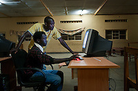 Young men use computer in telecentre in Kabaya, Rwanda. (Photo by Tadej Znidarcic)