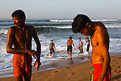 Tourists on the beach after taking an early morning bath in Bay of Bengal in Puri, Orissa, India. A dip in its salty waters is believed to hold great religious significance, as a result these golden sand beaches sees is a never-ending rush of pilgrims and tourists. Photo: Sanjit Das/Panos