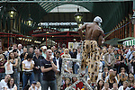 Street performer balancing chairs Covent Garden London UK